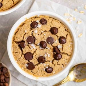 Baked oats topped with sea salt flakes with chocolate chips and a spoon beside.