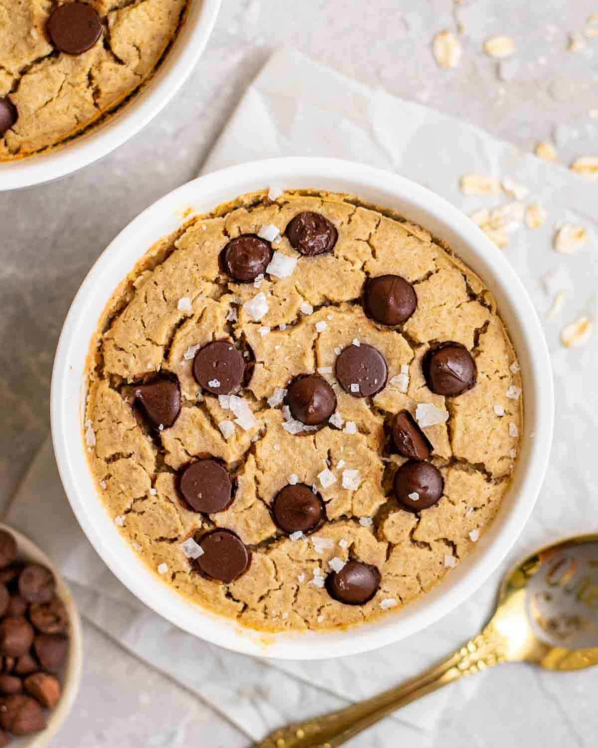 Baked oats in a ramekin topped with chocolate chips and sea salt with spoon beside.