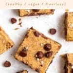 Blondies slices on a parchment paper with chocolate chips in the background.