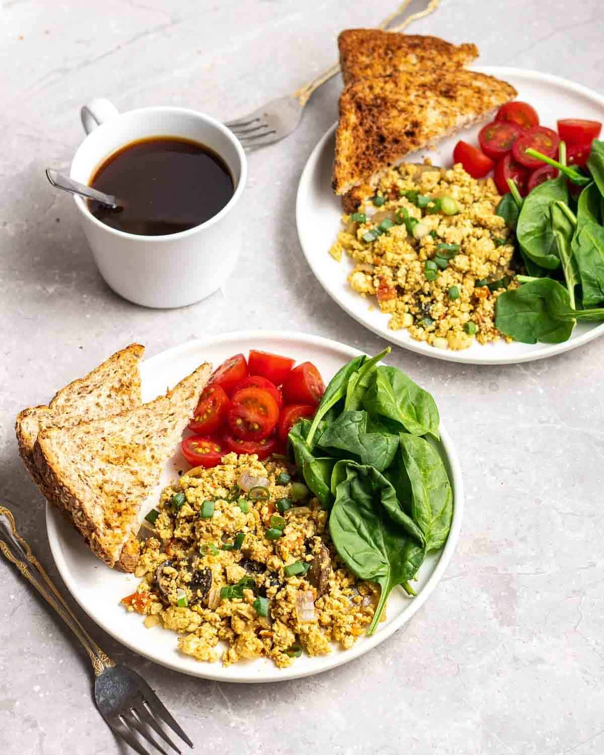 2 plates filled with tofu scramble, chopped tomatoes, spinach and toast with coffee in the background.