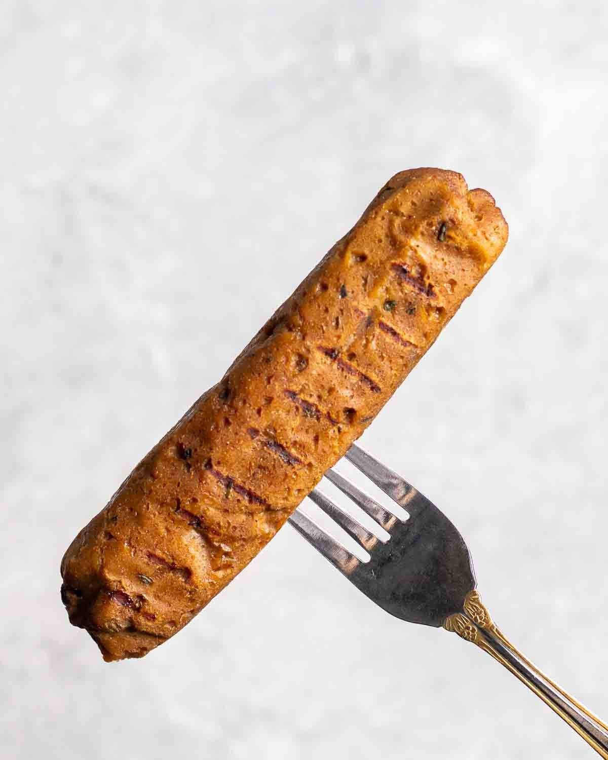 Fork holding a vegan Italian sausage on a grey background.
