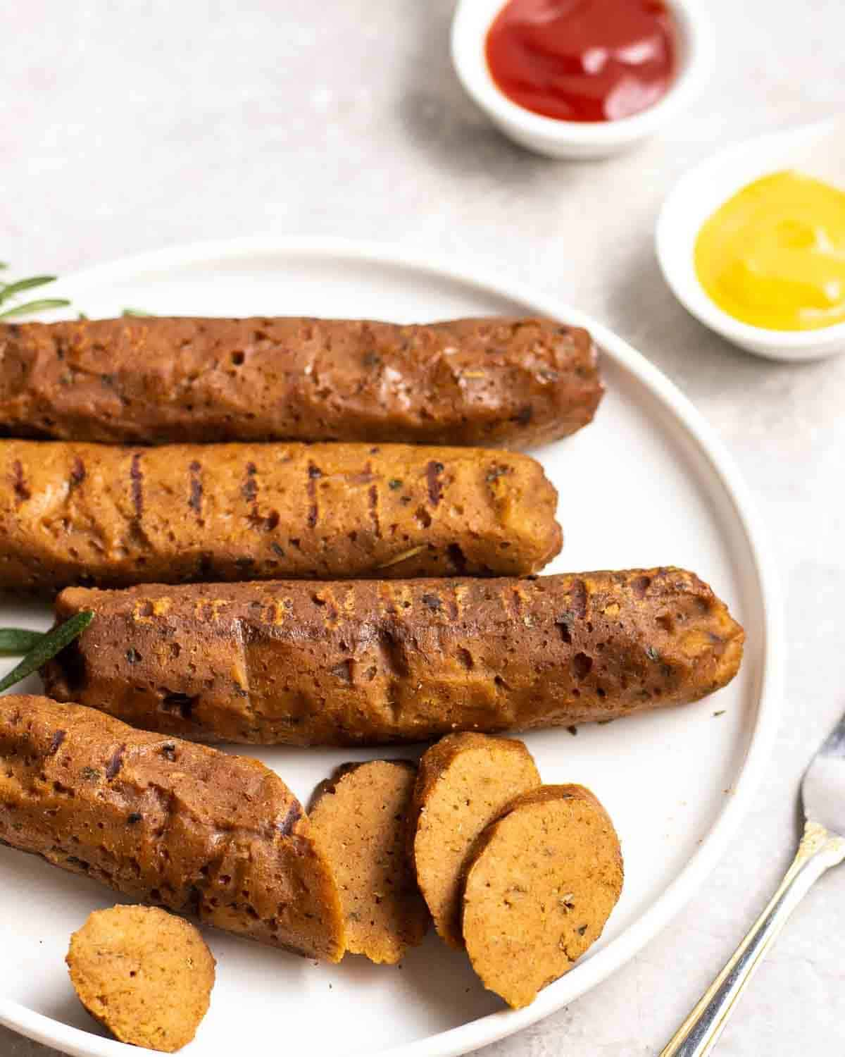 4 seitan sausages on a plate with the first one partially sliced.