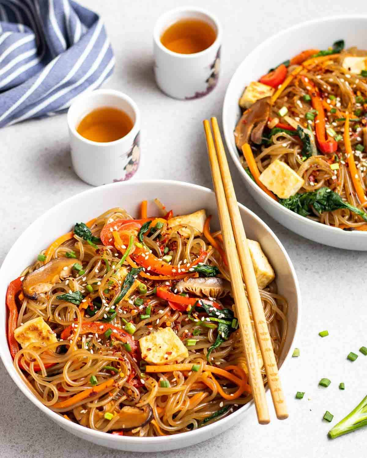2 plates of japchae in a deep plate served with tea with a blue striped tablecloth in the background.