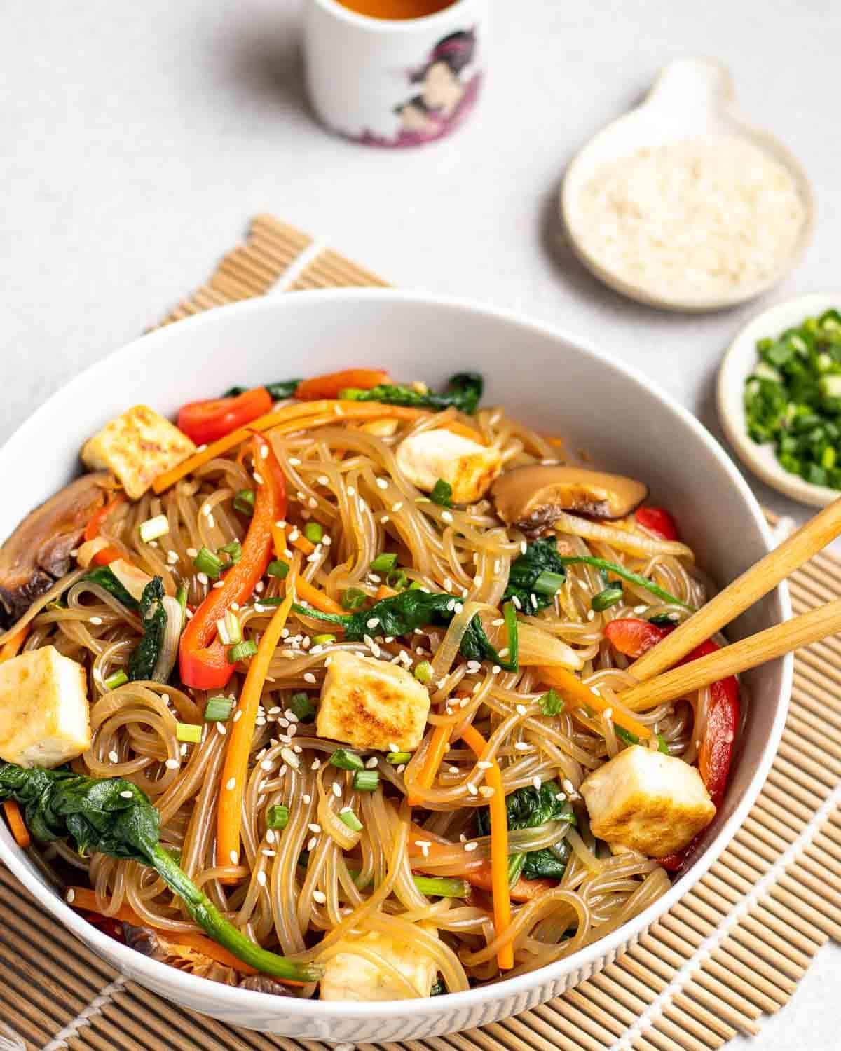 Japchae in plate with chopsticks. There are dishes of chopped scallions and sesame seeds, and a cup of tea in the background.