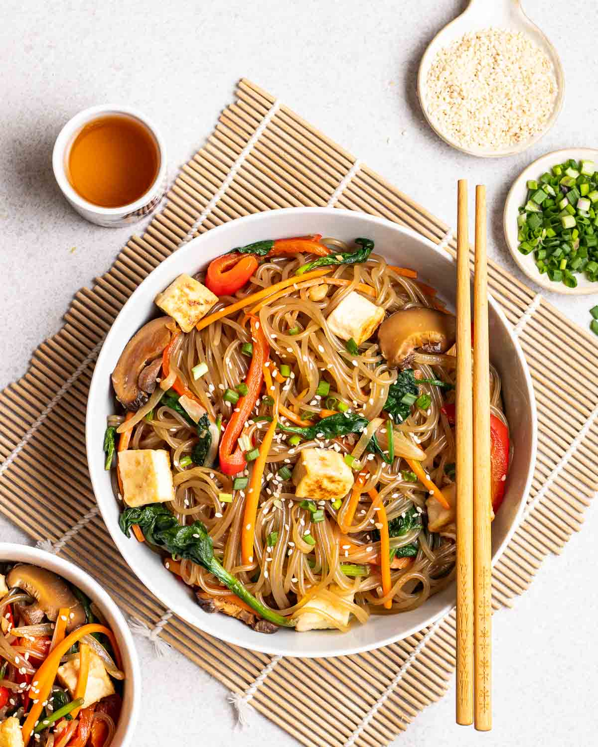Japchae served in a deep plate with a chopstick with cup of tea, sesame seeds and chopped scallions beside it.
