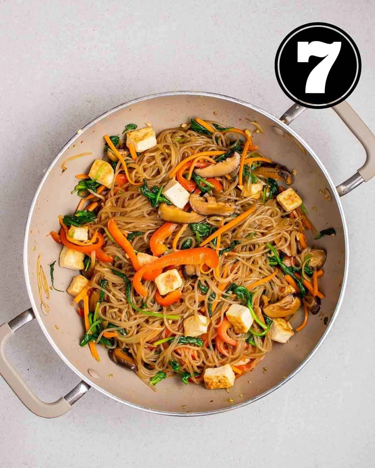Japchae with tofu cubes in a wok on a grey background.