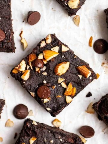 Slices of brownies arranged on a parchment paper with chocolate chips in the background.