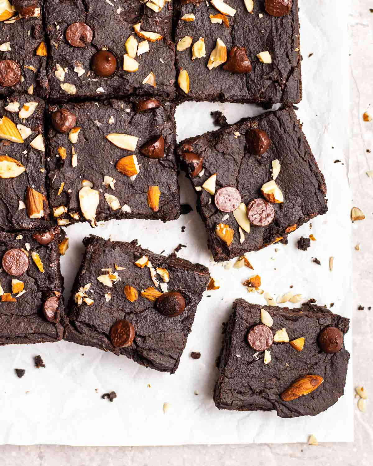 A tray of brownies on a parchment paper topped with chopped almonds and chocolate chips.