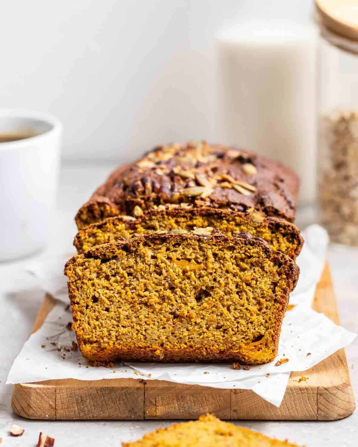 Partially sliced pumpkin banana bread on a wooden board lined with parchment paper.
