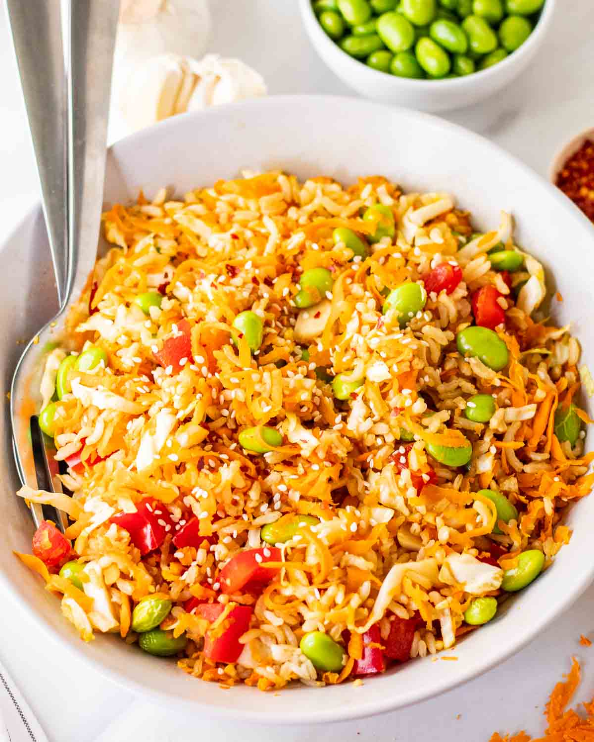 Rice salad in a bowl with fork and spoon on the side. There is a bowl of edamame in the background.