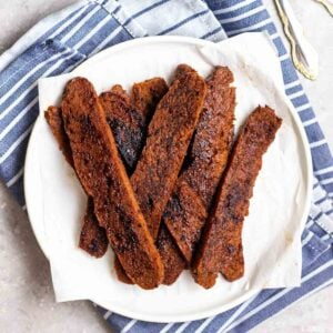 Strips of seitan bacon on a plate lined with parchment paper on a blue teacloth.