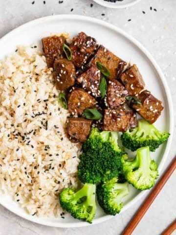 Plate filled with rice, vegan teriyaki chicken and broccoli with chopsticks beside.