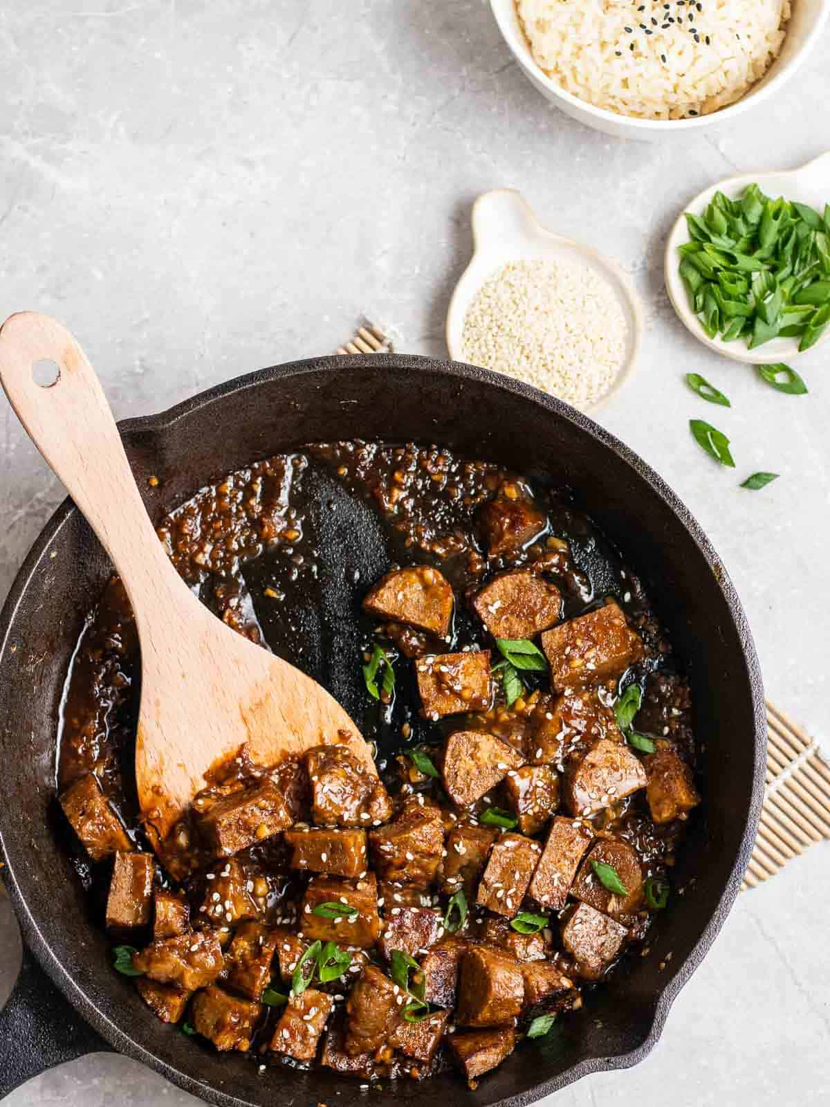 Vegan teriyaki chicken in a pan with wooden spatula topped with chopped green onion.
