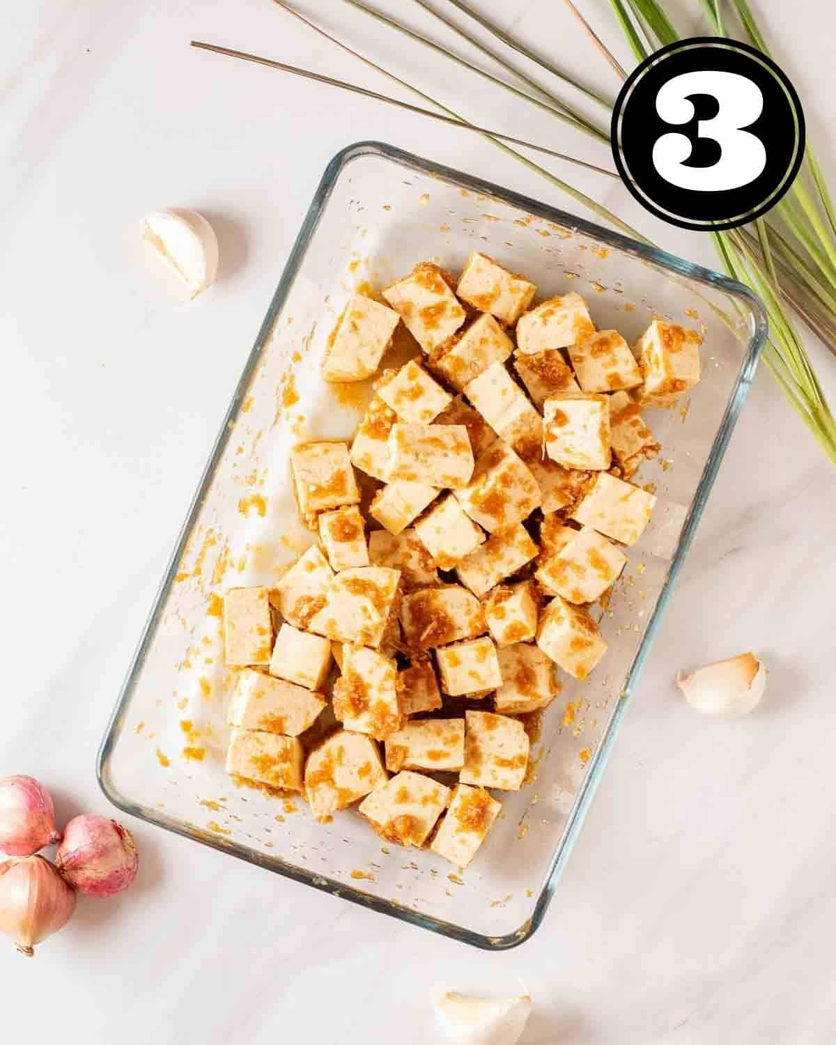 Marinating tofu cubes in a glass dish with lemongrass, garlic and shallots beside.