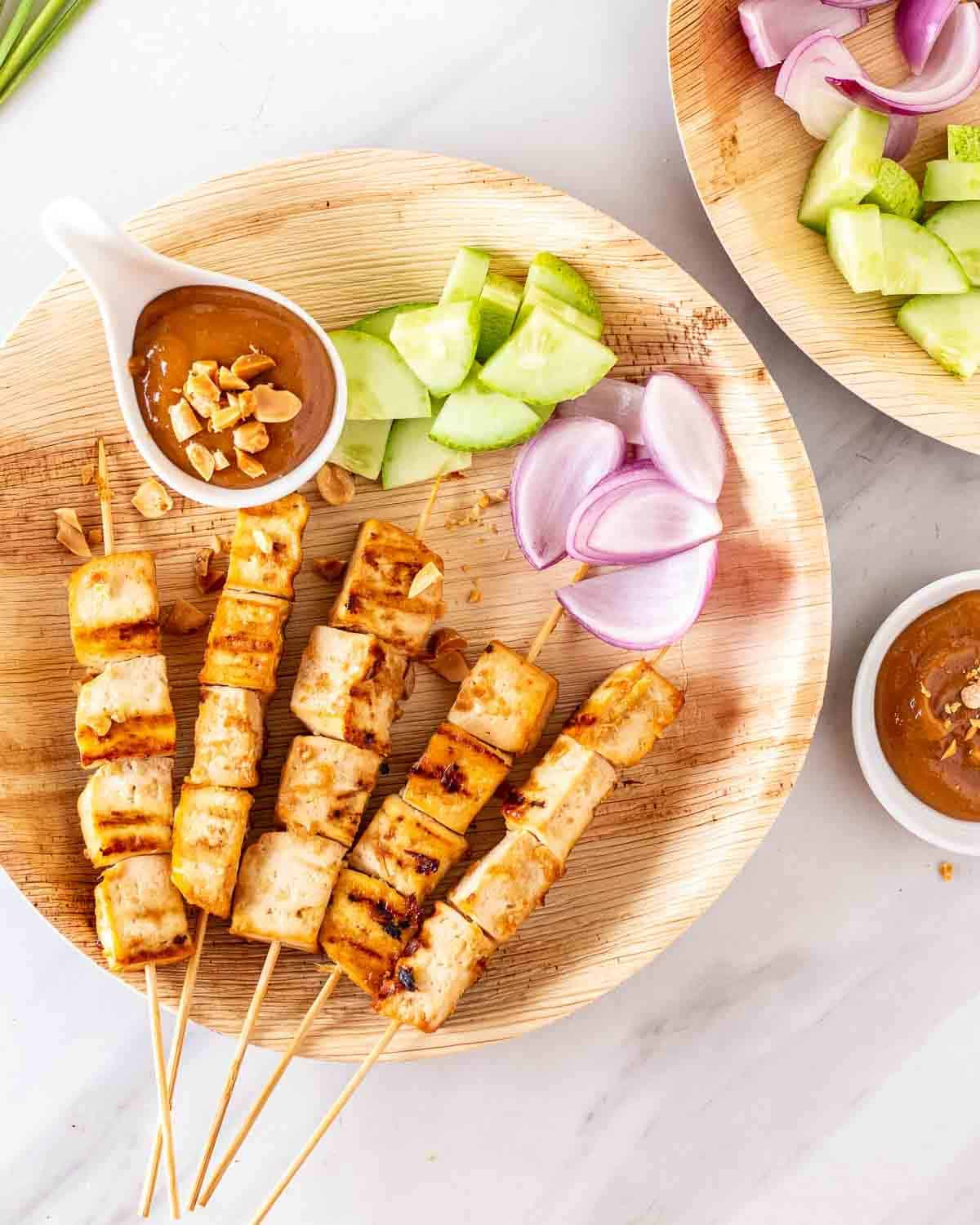 Satay skewers served with peanut sauce and chopped raw veggies in a brown plate.