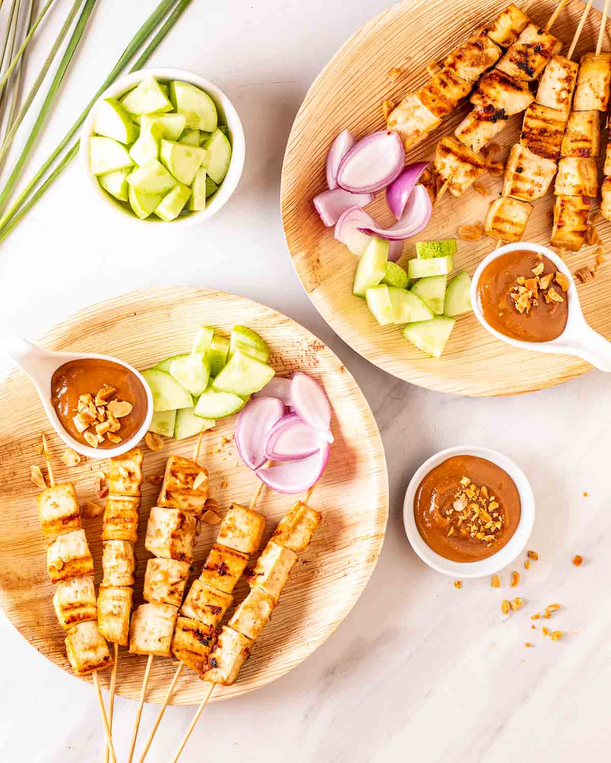 2 plates of tofu skewers served with peanut sauce with cucumber, lemongrass and peanut sauce in the background.
