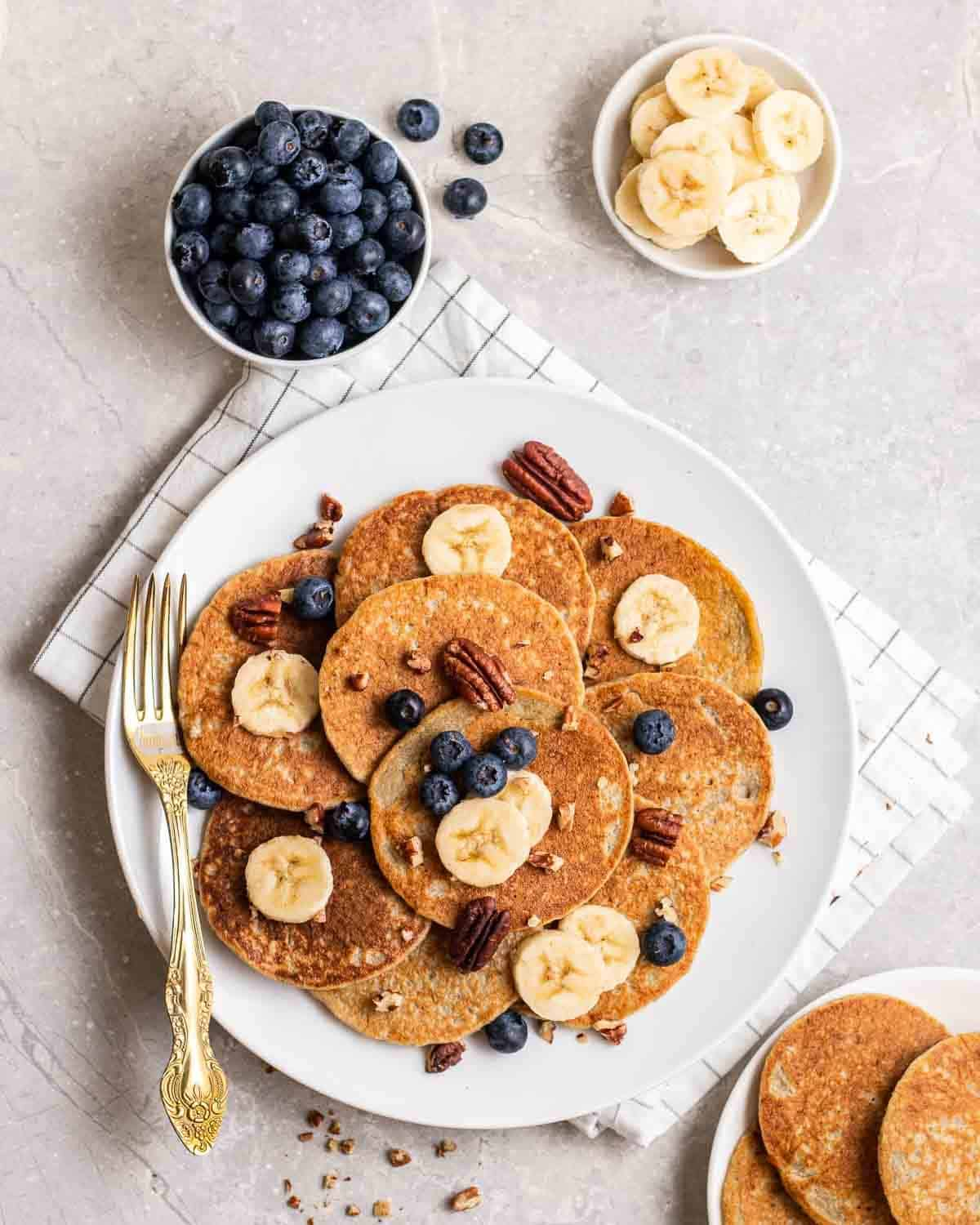 A plate of pancakes topped with sliced banana, blueberries and pecans with a fork beside.