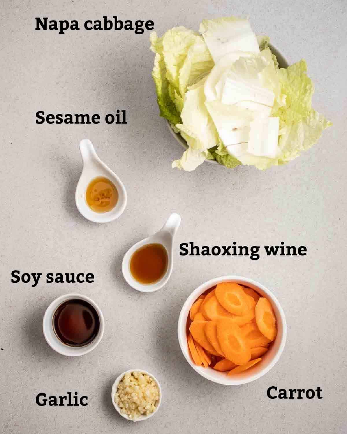 Ingredients needed like napa cabbage, carrot, garlic and seasonings in bowls on a grey background.