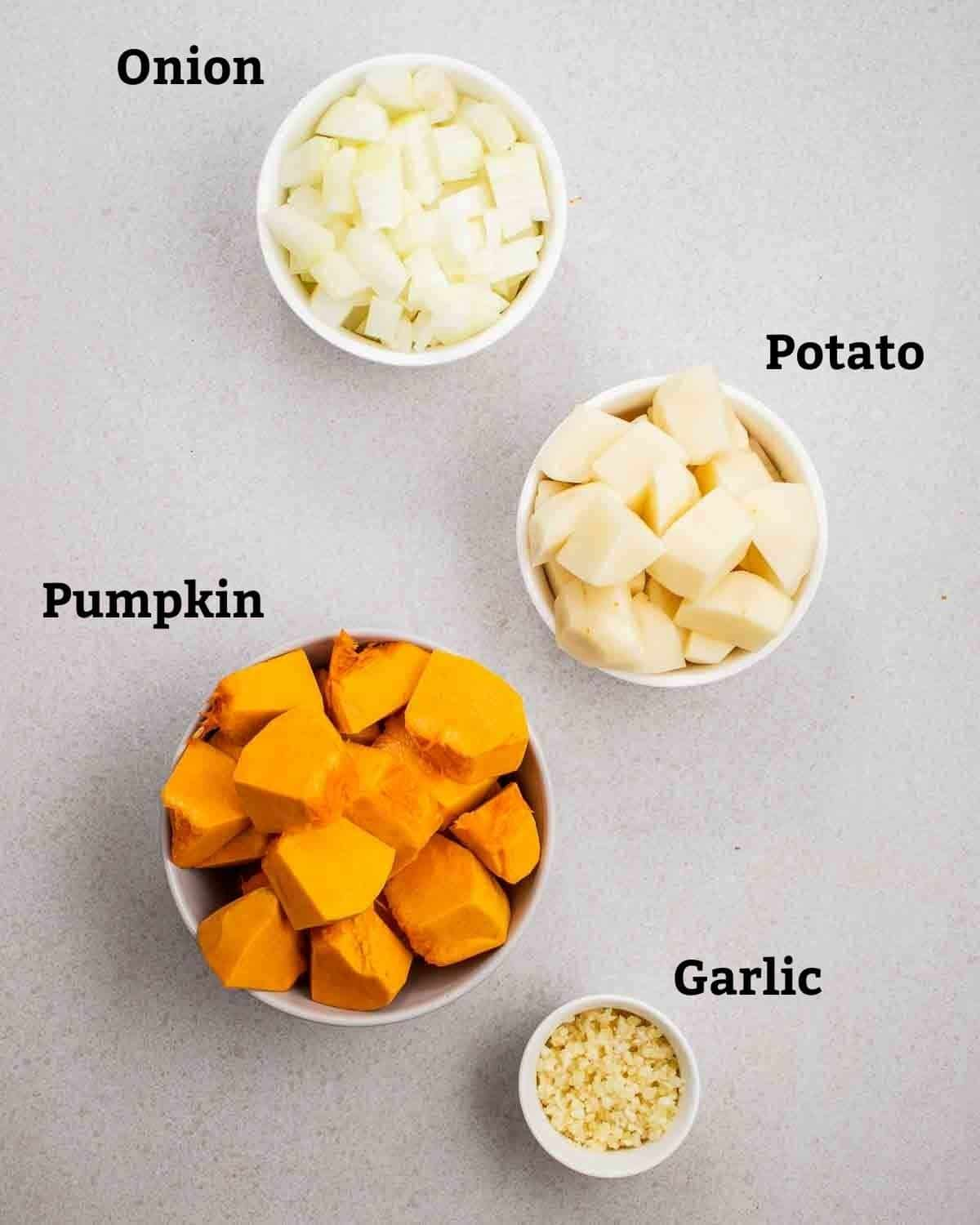 Ingredients needed like pumpkin, potato, onion and garlic in bowls on a grey background.