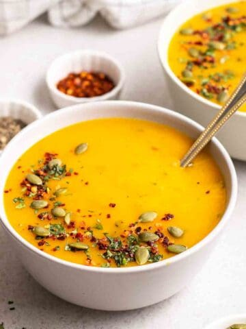 2 bowls of pumpkin potato soup with small dishes of chili flakes and black pepper in the background.