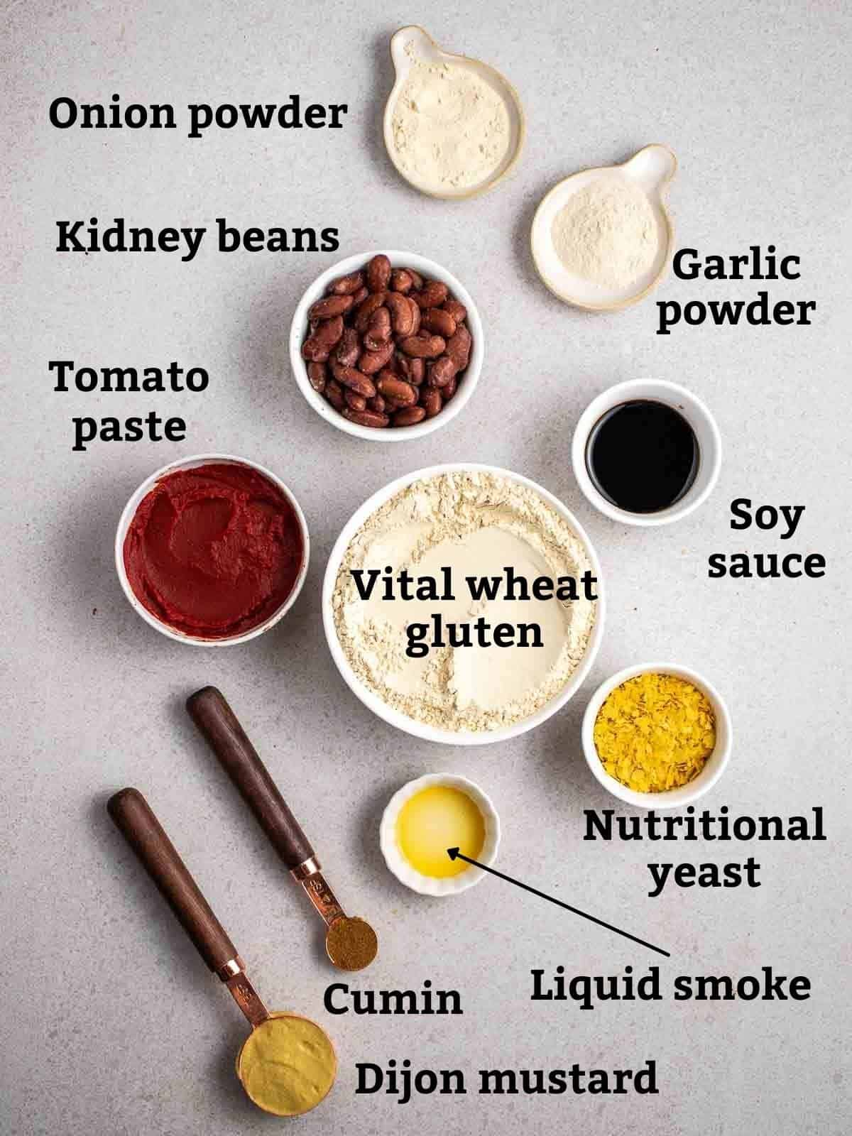 Ingredients needed like vital wheat gluten, beans, tomato paste and other seasonings in bowls on a grey background.