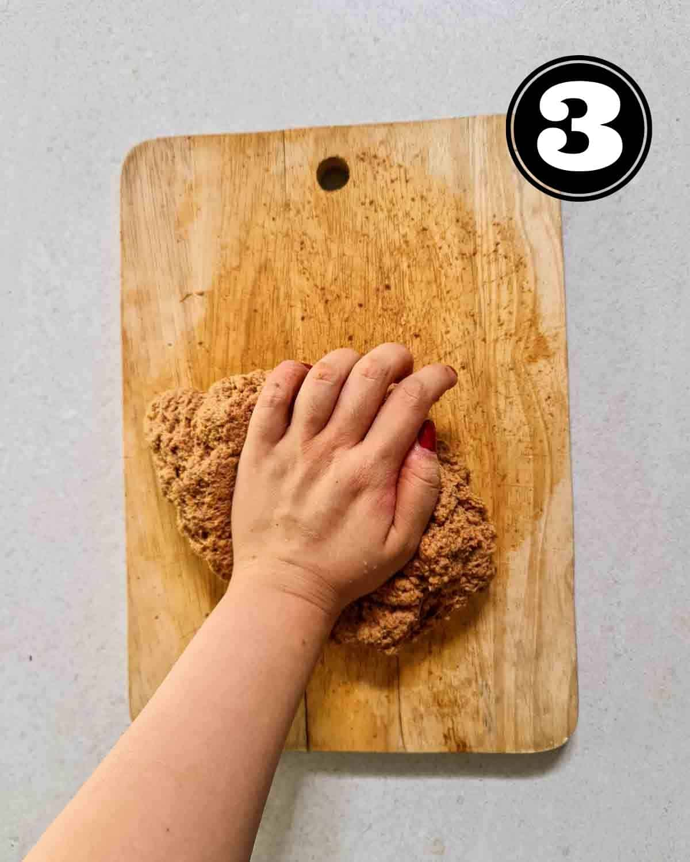 Kneading dough of seitan on a wooden chopping board.