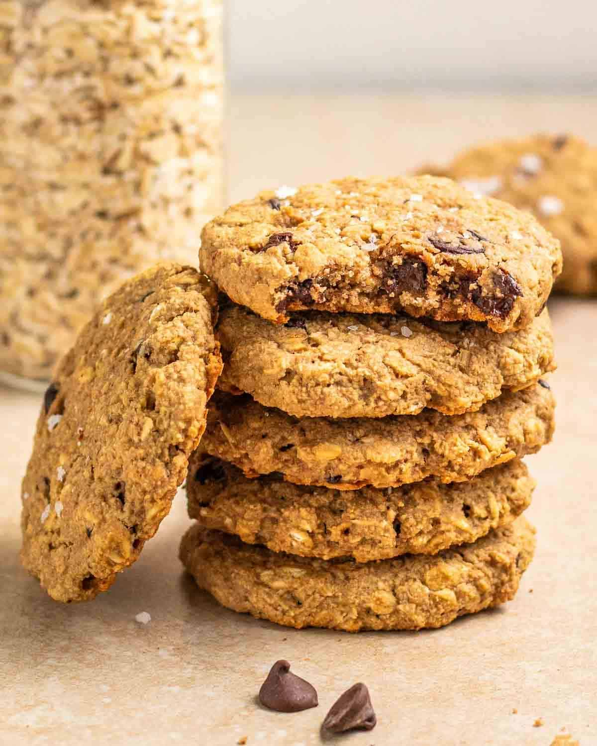 A stack of applesauce cookies with a jar of oats and more cookies in the background.