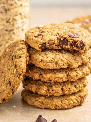 A stack of 5 oatmeal cookies with jar of oats and more cookies in the background.