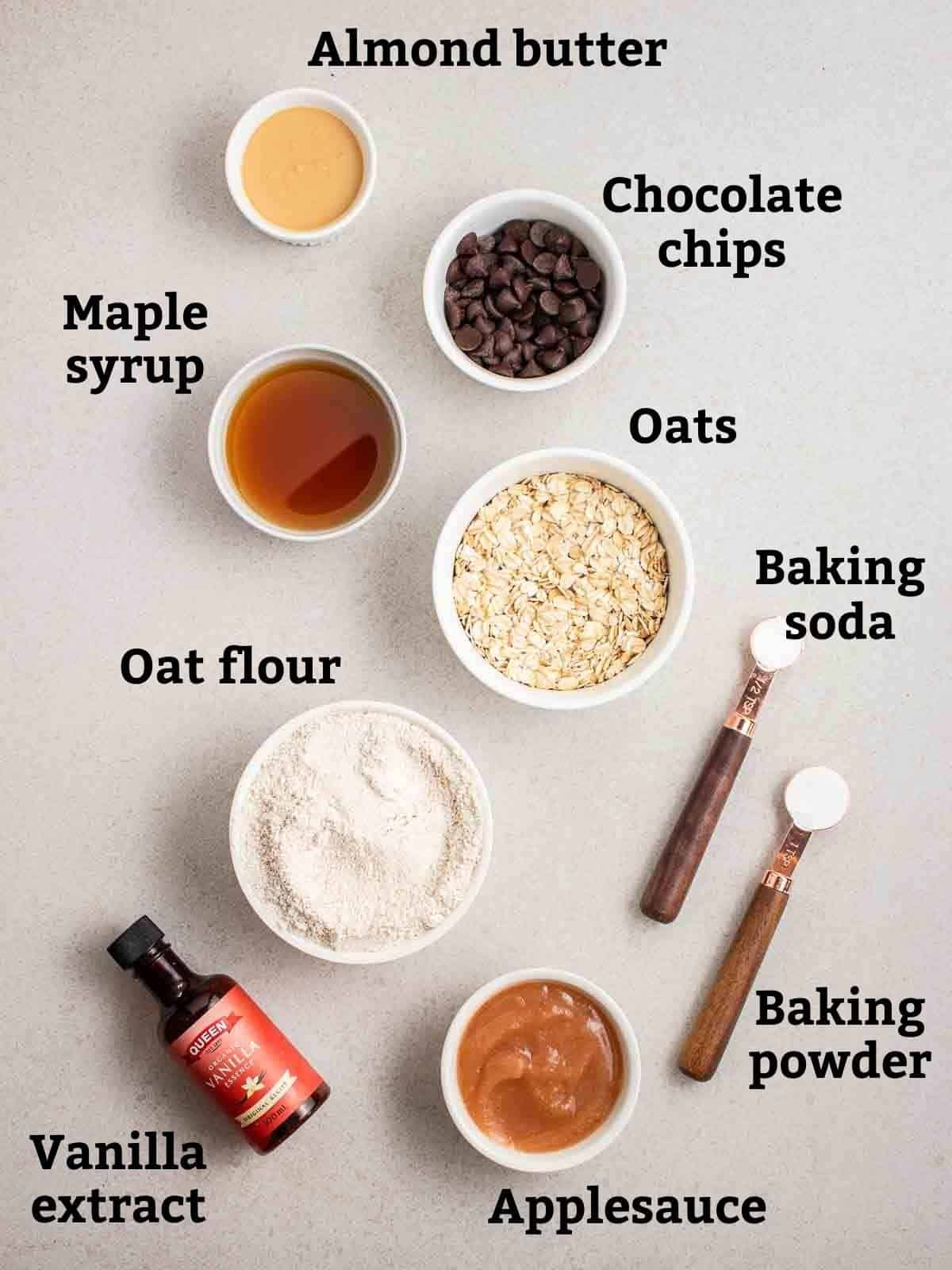 Ingredients needed like flour, oats, applesauce, maple syrup and almond butter on a grey background.
