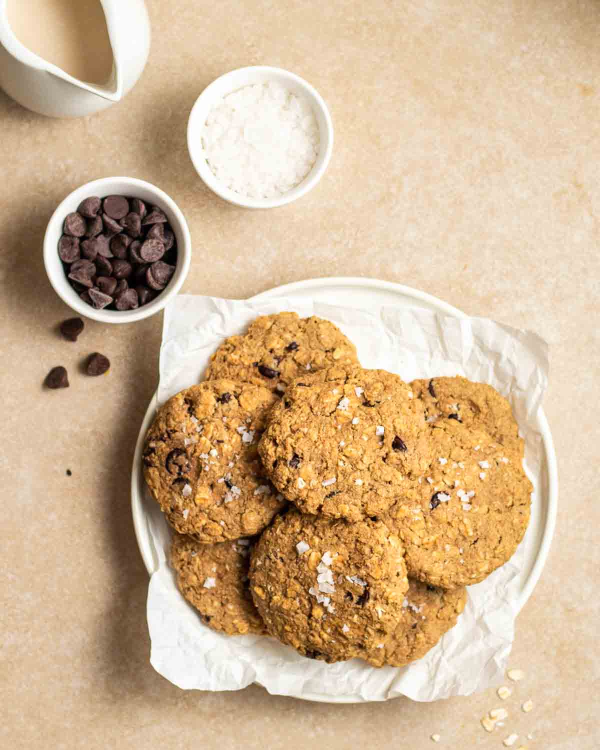 Plate filled with cookies with ramekin filled with chocolate chips, sea salt and jug of milk beside.