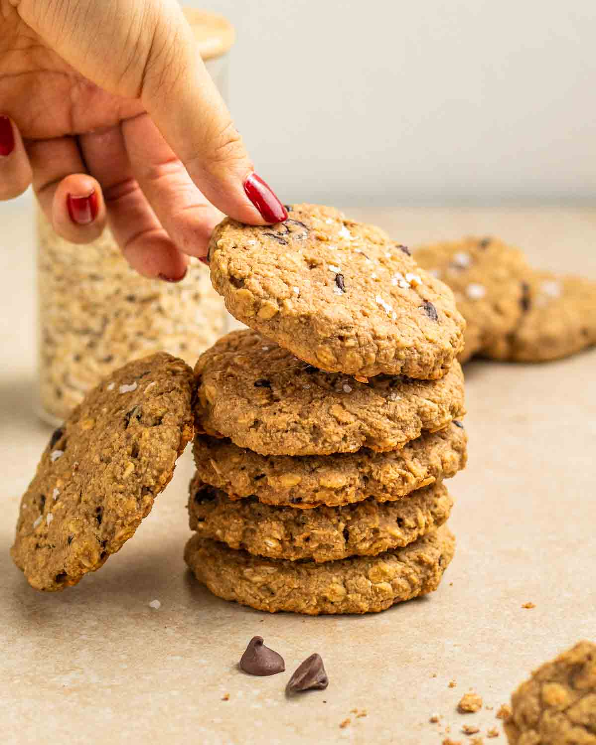 Taking out a cookie from a stack of them with jar of oats and more cookies in the background.