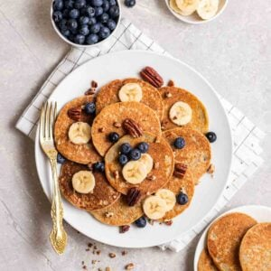 Banana pancakes arranged on a plate with a fork beside topped with blueberries, banana slices and pecans.