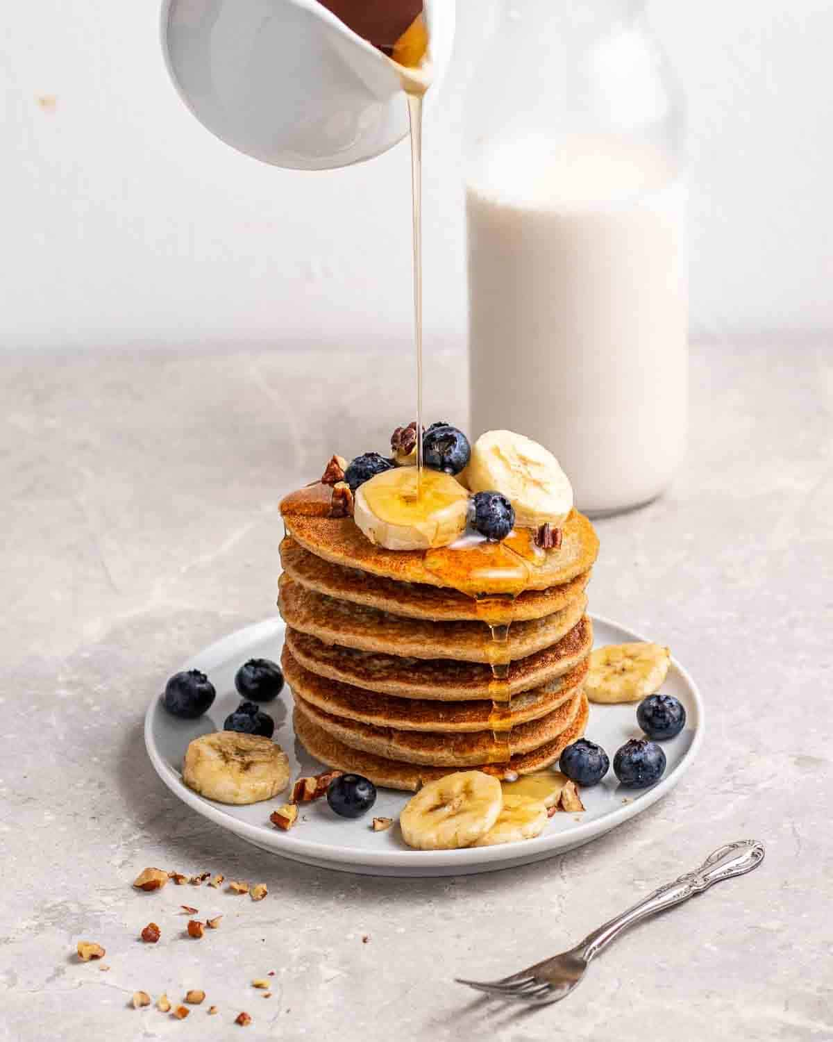 Pouring maple syrup on a stack of pancakes with a fork beside.