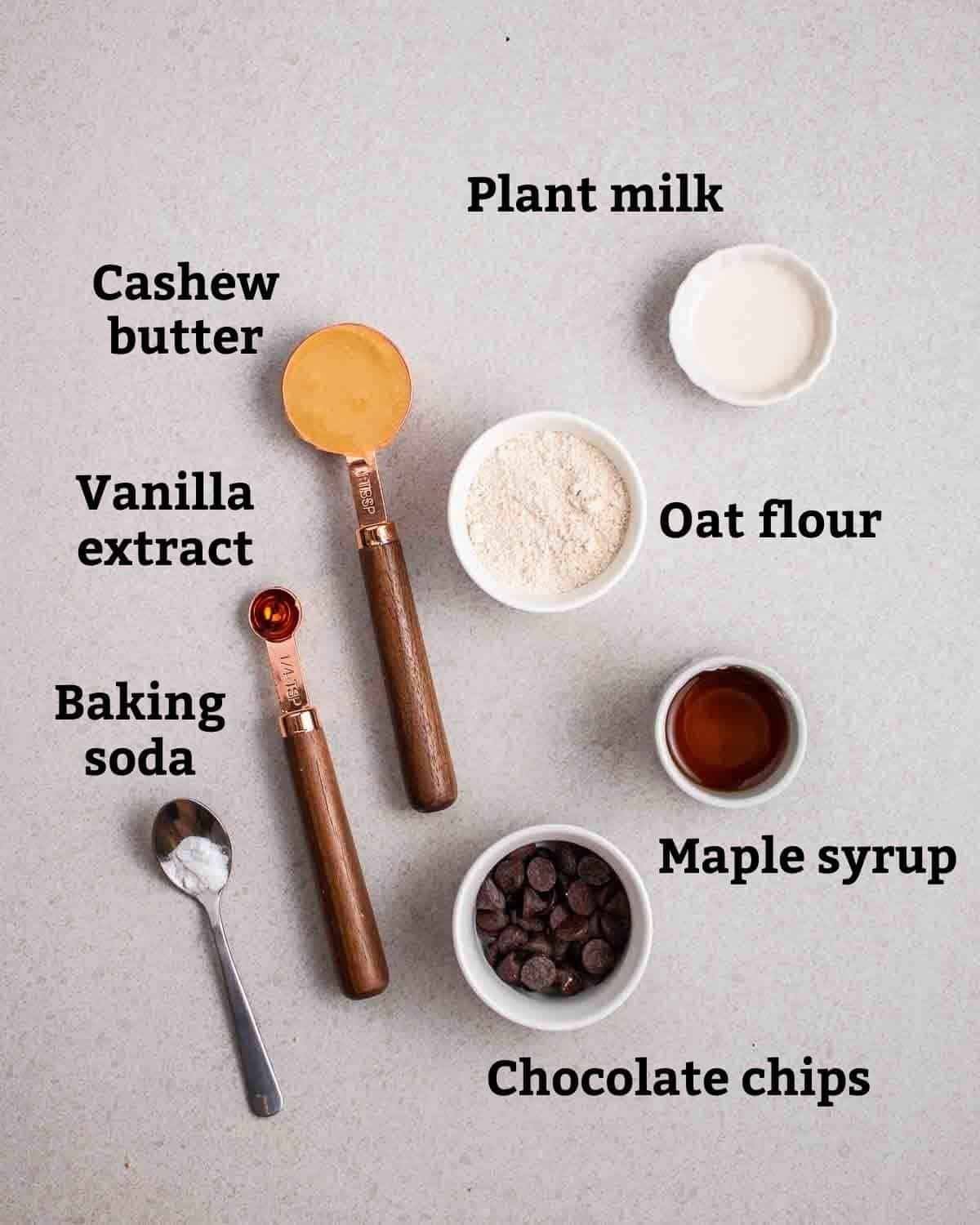 Ingredients needed like oat flour, maple syrup, cashew butter and milk on a grey background.
