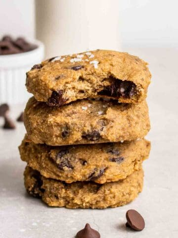 A stack of cookies with chocolate chips and jar of milk in the background.